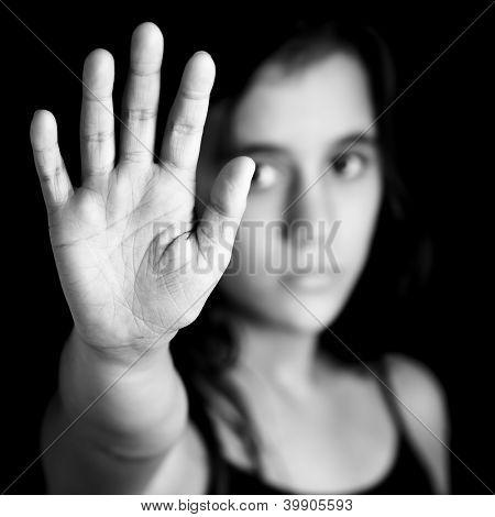 Imagem preto e branco de uma menina com a mão estendida de sinalização parar útil a campanha contra