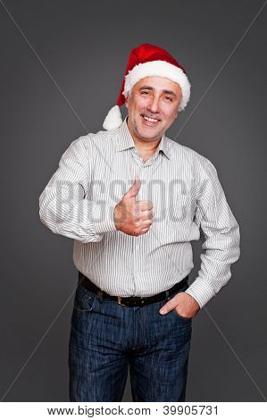 excited senior man in santa claus hat showing thumbs up and smiling over grey background
