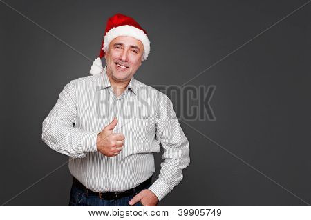 smiley senior man in santa hat standing near empty copyspace and showing thumbs up. studio shot over grey background