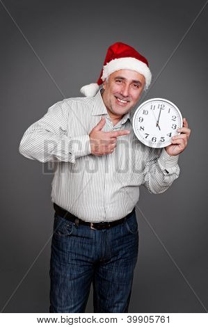 man in red christmas hat pointing finger at the clock and smiling. studio shot over dark background