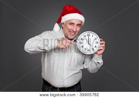 senior man in the santa hat pointing at the clock. studio shot over grey background