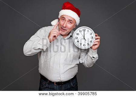 senior man in santa hat holding clock and showing the attention sign. studio shot over grey background