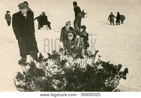 Vintage photo of father and children enjoying winter (fifties)