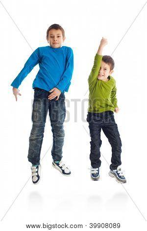 Two boys jumping on white background. Studio shot.