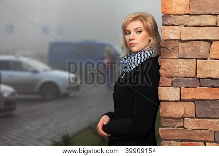 Young woman against a brick wall on the city street