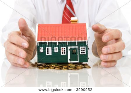 House On Golden Coins Pile With Businessman Hands