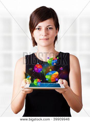 Mulher de negócios jovem olhando tablet moderno com gráficos coloridos
