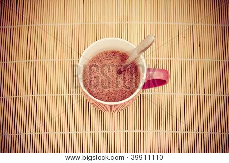 Pink Cup Of Hot Chocolate On Bamboo Tablecloth