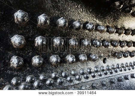 Black rivets in perspective on a train engine boiler