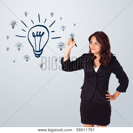 Young woman drawing light bulb on whiteboard