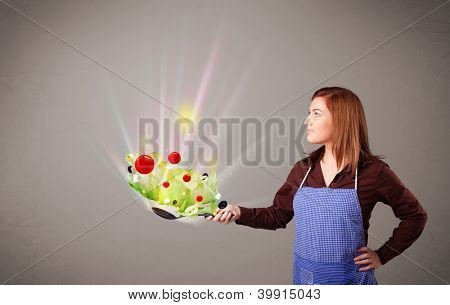 Beautiful young woman cooking fresh vegetables with abstract lights