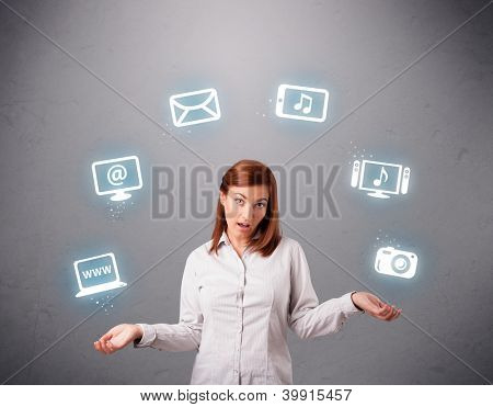 pretty girl standing and juggling with elecrtonic devices icons