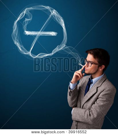 Handsome young man smoking unhealthy cigarette with no smoking sign