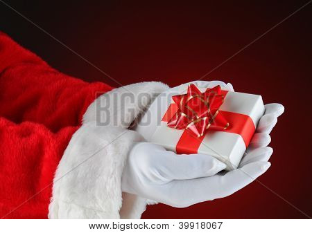 Santa Claus holding a small Christmas Present in both of his hands. Horizontal format showing only hand and arms on a light ot dark red background.