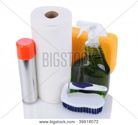 Cleaning supplies on a white background. An assortment of paper towels, brush, sponge and cleaners viewed from a high angle.