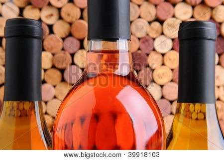 Closeup of three wine bottles two chardonnay and one red in front of a mass of out of focus corks.