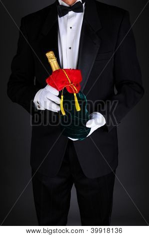 Gentleman wearing a tuxedo holding a champagne bottle wrapped up in a festive holiday gift bag. Man is unrecognizable on a light to dark gray background.