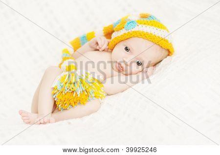 Newborn Baby Close Up In Woolen Hat Over White Soft Background.