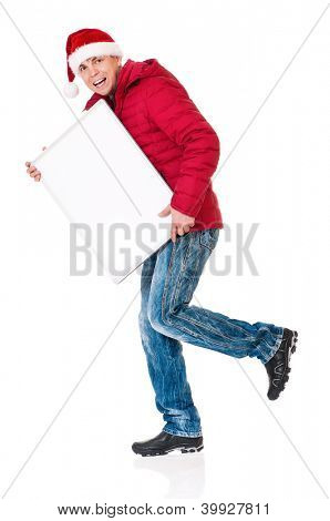 Full length portrait of a young man in winter clothing and Santa hat with empty white board isolated on white background
