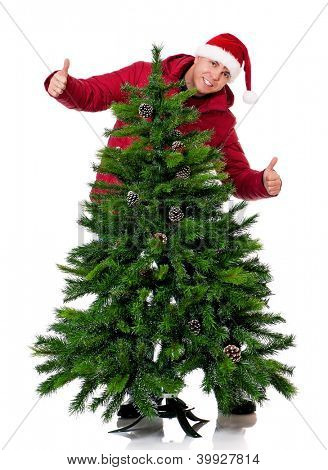 Full length portrait of a young man in winter clothing and Santa hat with artificial fir tree isolated on white background