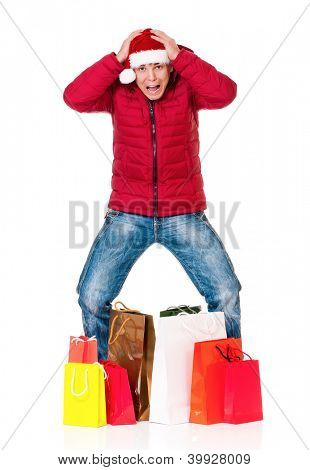 Full length portrait of a young man in winter clothing and Santa hat with shopping bags isolated on white background