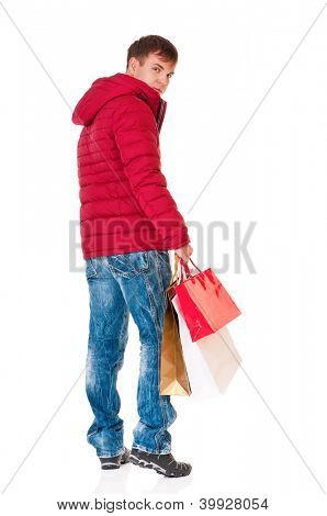 Full length portrait of a young man in winter clothing with shopping bags isolated on white background