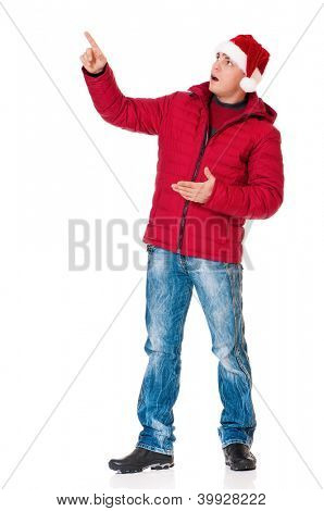 Full length portrait of a young man in winter clothing with Santa hat showing something isolated on white background