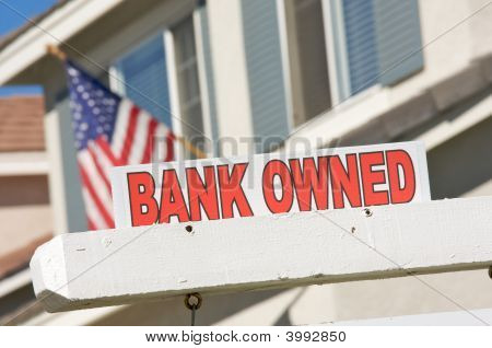 Bank Owned Real Estate Sign And House With American Flag