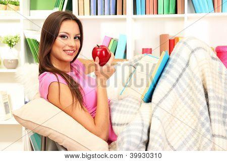Retrato de mujer comer manzana y libro de lectura mientras se está acostado en el sofá