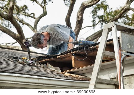 Hombre examinar y reparar el techo de la casa de fugas podrido