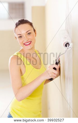 happy young woman painting new home with paint roller