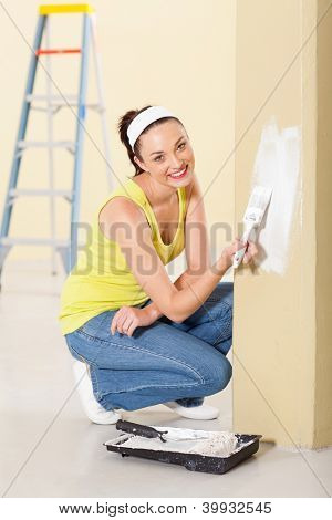 happy young woman painting new home