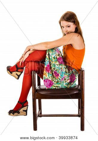 The Girl In Red Tights Sits In An Old Wooden Chair