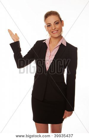 Smiling stylish young business woman pointing with her hand towards blank copyspace, three quarter studio portrait on white