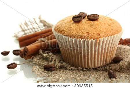 tasty muffin cake on burlap, spices and coffee seeds, isolated on white