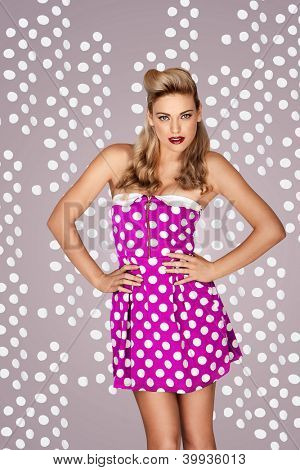 Beautiful blonde retro fashion model in a pink polka dot dress posing in front of a studio background with dots