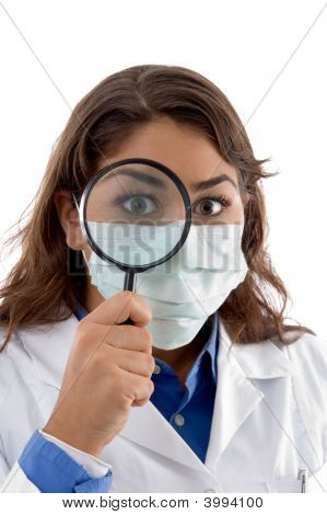 Female Doctor Inspecting With Magnifying Glass