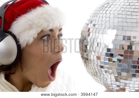 Surprised Woman Looking To Disco Ball And Wearing Christmas Hat