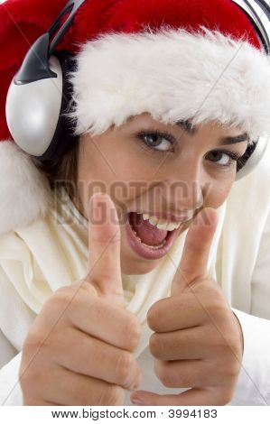 Woman Wearing Christmas Hat And Showing Thumbs Up