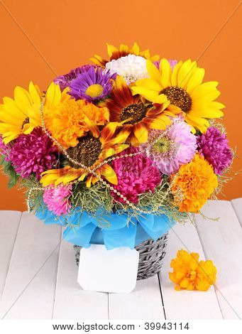 Beautiful bouquet of bright flowers with paper note on wooden table on orange background