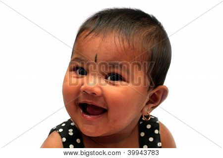 Happy & Joyful Healthy Indian Baby Girl Smiling. The Photo Is Taken With Studio Lights And On White