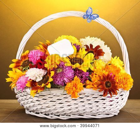 Beautiful bouquet of bright flowers in white basket on wooden table on yellow background