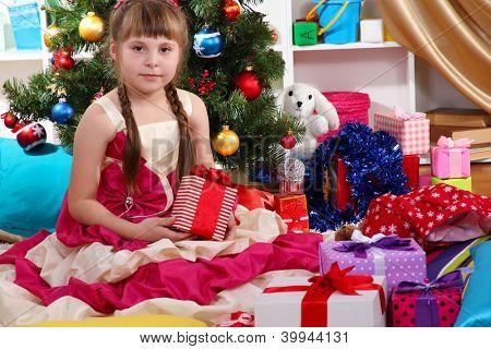 Menina bonita no vestido de férias com presente em suas mãos no quarto festivamente decorado
