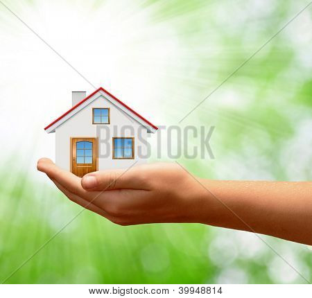 The house in hands on green natural backgorund