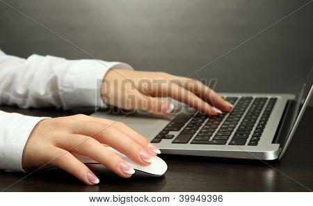 female hands writing on laptot, on grey background