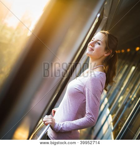 Young woman traveling by train, watching the passing country side while standing in the train corridor