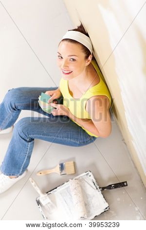 above view of young woman choosing paint color for her new home