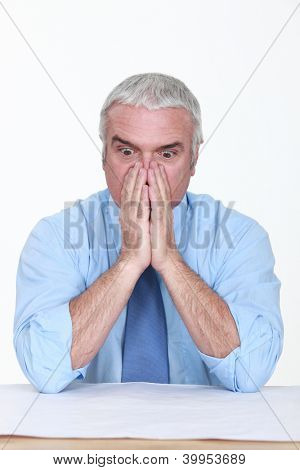 Appalled man looking at a blueprint