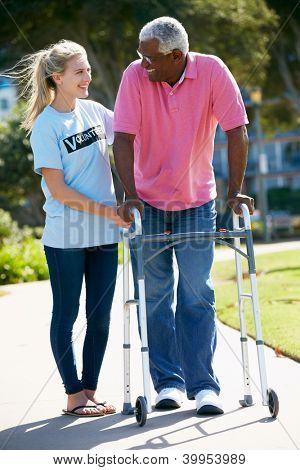Teenage Volunteer Helping Senior Man With Walking Frame