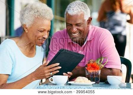 Senior Couple Using Tablet Computer At Outdoor Cafe